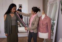 Fashion designer measuring lengths of customer in studio. — Stock Photo