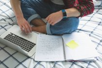 Sezione bassa di uomo utilizzando laptop a letto con notebook . — Foto stock