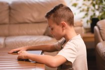 Boy using digital tablet in living room at home — Stock Photo