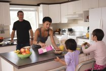 Family having breakfast at table in kitchen — Stock Photo