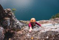 Scalatrice di roccia femminile che scala la montagna rocciosa vicino al lago — Foto stock