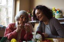 Улыбающаяся пожилая женщина, взаимодействующая со смотрителем в доме престарелых — стоковое фото