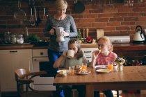 Avó, servindo café da manhã para netas na cozinha — Fotografia de Stock