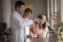 Teacher assisting students in chemical experiment at laboratory — Stock Photo