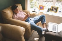 Man using mobile phone while resting on sofa in living room at home. — Stock Photo
