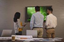 Rückansicht von Geschäftsleuten, die im Konferenzraum im Büro Graphik auf dem Bildschirm diskutieren. — Stockfoto