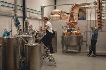 Operaio femminile controllo macchina della distilleria in fabbrica — Foto stock