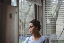 Nachdenkliche Frau, die zu Hause aus dem Fenster schaut — Stockfoto