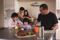 Familia desayunando en la mesa en la cocina - foto de stock
