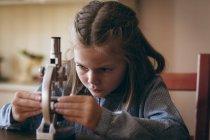 Fille mignonne expérimentant avec microscope à la maison — Photo de stock