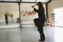 Karate fighter practicing with long pole in fitness studio. — Stock Photo