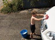 Хлопчик пральна машина на зовнішніх гараж сонячний день — стокове фото