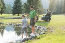 Father and son playing near pond in the course — Stock Photo
