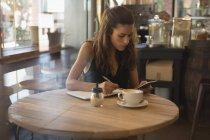 Femme à l'aide de téléphone portable lors de l'écriture sur le journal dans le café-restaurant — Photo de stock