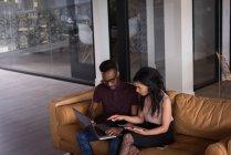Офіс колегами, обговорювати над ноутбуком на дивані в офісі — стокове фото