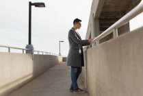 Thoughtful man using mobile phone on bridge — Stock Photo