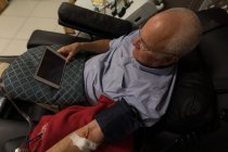 Senior man using digital tablet while donating blood in blood bank — Stock Photo