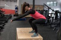 Junge Frau Kniebeugen trainieren im Fitness-studio — Stockfoto