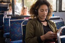 Young female commuter listening music while travelling in modern bus — Stock Photo