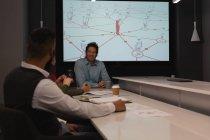 Uomini d'affari che interagiscono nella sala conferenze dell'ufficio — Foto stock