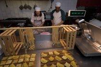 Male and female baker preparing pasta in bakery — Stock Photo
