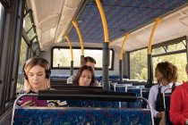 Female commuter listening music while travelling in modern bus — Stock Photo