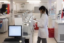 Laboratory technician writing on clipboard in blood bank — Stock Photo