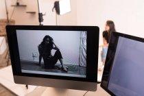 Modelo feminino posando na tela do computador no estúdio de fotos — Fotografia de Stock