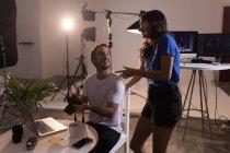Мужчина-фотограф и женщина-модель взаимодействуют друг с другом в фотостудии — стоковое фото