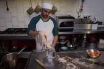 Usar la máquina para preparar pasta en panadería panadero - foto de stock