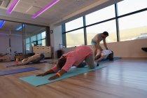 Тренер, помогающий старшим женщинам в йоге в центре йоги — стоковое фото