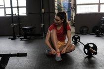 Schöne Frau, die Schnürsenkel zu binden, im Fitness-studio — Stockfoto