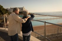 Senior couple standing at promenade near sea on a sunny day — Stock Photo