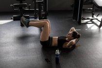 Красивая женщина делает хрусты в фитнес-студии — стоковое фото