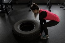 Fit woman exercising with tyre in fitness studio — Stock Photo