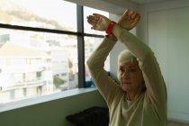 Старший жінка, що здійснює йога йога центр — стокове фото