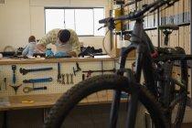 Homme, nettoyage des pièces de bicyclette sur le comptoir dans l'atelier — Photo de stock