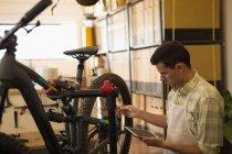 Man using digital tablet while repairing bicycle in workshop — Stock Photo