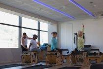 Trainer assisting senior women in performing yoga at yoga center — Stock Photo