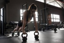 Beautiful woman doing push ups with kettle bell in fitness studio — Stock Photo