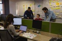 Donna di affari using computer portatile mentre colleghi che discutono in fondo all'ufficio — Foto stock
