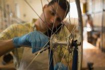 Крупный план человека, разговаривающего по мобильному телефону во время ремонта велосипедного колеса в мастерской — стоковое фото