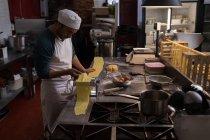 Бейкер, с помощью машины для приготовления макарон в пекарне — стоковое фото