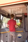 Young male commuter taking ticket from driver in modern bus — Stock Photo
