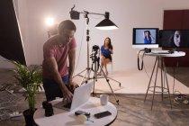 Мужчина фотограф, используя ноутбук в фото студии — стоковое фото
