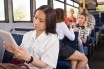 Female commuter using digital tablet while travelling in modern bus — Stock Photo