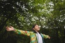 Junges Mädchen mit ausgestreckten Armen im Wald — Stockfoto