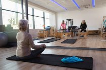 Grupo de mujeres mayores realizar yoga en centro de yoga - foto de stock