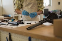 Mid section of man cleaning bicycle parts on counter in workshop — Stock Photo