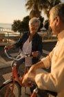 Coppia anziana parlando tra di loro al lungomare in una giornata di sole — Foto stock